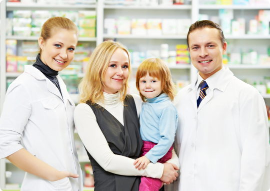 mother carrying her child standing in between two pharmacists