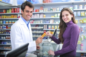 pharmacist handling a medicine tablet to a pharmacy customer